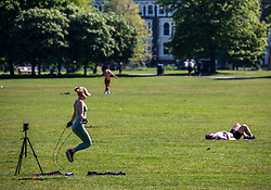 © Licensed to London News Pictures. 24/04/2020. London, UK. A women exercises in front of a camera while out in  the warm weather on Clapham Common during lockdown, were temperatures are expected to reach 22c over the weekend. London has seen an increase in traffic and busier High Streets as more shops and takeaway restaurants start to open up during the coronavirus pandemic crisis. Photo credit: Alex Lentati/LNP