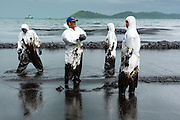 30 JULY 2013 - KOH SAMET, RAYONG, THAILAND:  Workers walk through oily surf on Ao Prao beach on Koh Samet. About 50,000 liters of crude oil poured out of a pipeline in the Gulf of Thailand over the weekend authorities said. The oil made landfall on the white sand beaches of Ao Prao, on Koh Samet, a popular tourists destination in Rayong province about 2.5 hours southeast of Bangkok. Workers from PTT Global, owner of the pipeline, and up to 500 Thai military personnel are cleaning up the beaches. Tourists staying near the spill, which fouled Ao Prao beach, were evacuated to hotels on the east side of the island, which was not impacted by the spill. PTT Global Chemical Pcl is part of state-controlled PTT Pcl, Thailand's biggest energy firm.     PHOTO BY JACK KURTZ