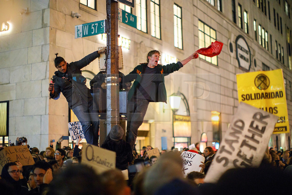 © Licensed to London News Pictures. 09/11/2016. New York, USA. Protesters climb a traffic light post as thousands of anti-Trump demonstrators protest outside Trump Tower after marching from Union Square in New York City, on Wednesday, 9 November 2016 following the presidential election won by Donald Trump. Photo credit: Tolga Akmen/LNP