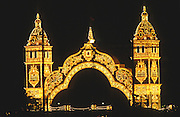 """The colorful entrance archway to the Feria park, with all the casetas, is decoratively painted and illuminated at night..The Feria de abril de Sevilla, """"Seville April Fair"""" dates back to 1847. During the 1920s, the feria reached its peak and became the spectacle that it is today. It is held in the Andalusian capital of Seville in Spain. The fair generally begins two weeks after the Semana Santa, Easter Holy Week. The fair officially begins at midnight on Monday, and runs six days, ending on the following Sunday. Each day the fiesta begins with the parade of carriages and riders, at midday, carrying Seville's citizens to the bullring, La Real Maestranza...For the duration of the fair, the fairgrounds and a vast area on the far bank of the Guadalquivir River are covered in rows of casetas (individual decorated marquee tents which are temporarily built on the fairground). Some of these casetas belong to the prominent families of Seville, some to groups of friends, clubs, trade associations or political parties. From around nine at night until six or seven the following morning, at first in the streets and later only within each caseta, crowds of people party and dance Sevillanas, traditional Flamenco dances, Sevillan style drinking Jerez sherry, or Manzanilla wine, and eating tapas. Men and women dress up in their finery, the traditional """"traje corto"""" (short jacket, tight trousers and boots) for men and the """"faralaes"""" or """"trajes de flamenca"""" (flamenco style dress) for women. The men traditionally wear hats called """"cordobés""""."""