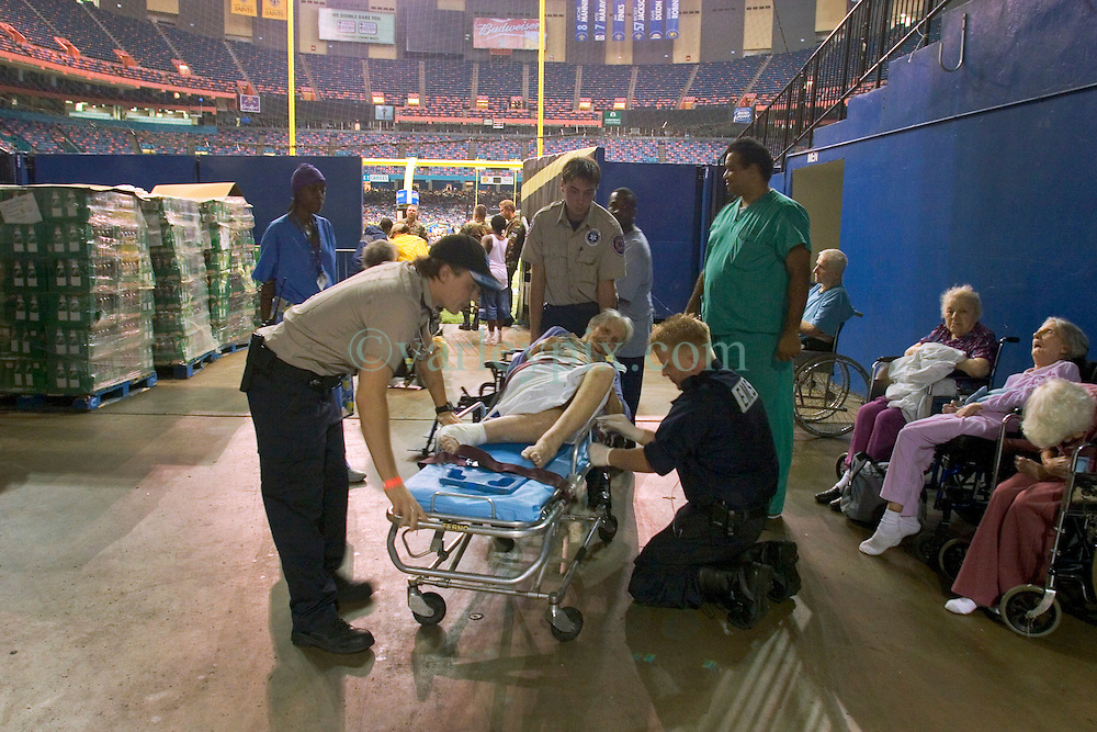 28th August, 2005. Hurricane Katrina, New Orleans, Louisiana. Thousands of people sought shelter inside the New Orleans Saints' Superdome the night before the storm hit. Elderly and infirm patients, taken from hospitals and nursing homes were pushed against walls leading to the playing surface. An elderly lady recieves treatment at the makeshift traige area next to the playing field.