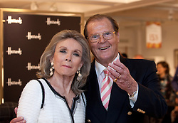 © Licensed to London News Pictures. 11/10/2012. London, U.K..Actor Roger Moore ® and his wife Kristina Tholstrup  At Harrods Store in knightsbridge, London, today (11/10/2012). The James Bond legend appears in store to sign copies of his new book, Bond on Bond (published October 4)..Photo credit : Rich Bowen/LNP