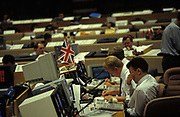A currency banker with the British Union Jack above his desk, rubs tired eyes while working in front of 90s computers in the currency trading floor of National Westminster Bank PLC in the City of London, the capitals financial centre, on 20th May 1992, in London, England. Screens glow with the most up to date trading figures and news items allowing traders to react instantly on the money markets.