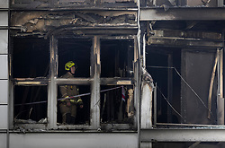 © Licensed to London News Pictures. 07/05/2021. London, UK. A fire fighter inspects the charred remains of apartments at New Providence Wharf in Poplar in east London. 100 fire fighters and 20 crews tackled the blaze at it's peak. Photo credit: Peter Macdiarmid/LNP
