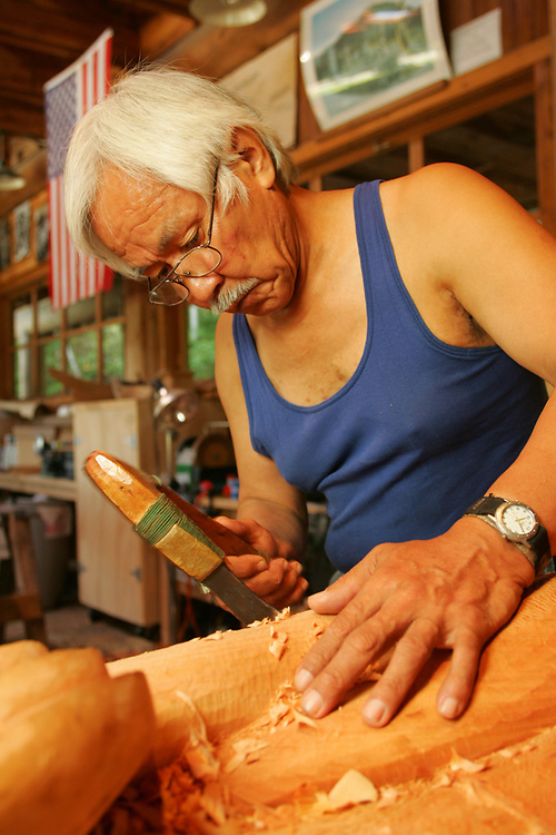 Tlingit/Haida Master Carver, Nathan Jackson, uses an adz to carve a totem at the carving shed in Saxman, Alaska.