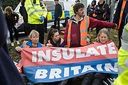 Insulate Britain climate activists sit on a verge with a banner after blocking a M25 slip road at Junction 14 close to Heathrow airport as part of a campaign intended to push the UK government to make significant legislative change to start lowering emissions on 27th September 2021 in Colnbrook, United Kingdom. The activists are demanding that the government immediately promises both to fully fund and ensure the insulation of all social housing in Britain by 2025 and to produce within four months a legally binding national plan to fully fund and ensure the full low-energy and low-carbon whole-house retrofit, with no externalised costs, of all homes in Britain by 2030.
