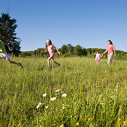 A woman and three young girls walk in a field in Sabins Pasture in Montpelier, Vermont.