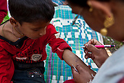 As each child arrives a number is written on their arm to determine their place in the queue. To begin with the volunteer health worker takes their temperature and writes it on the child's forearm.  The children are at a mobile health clinic in the Gagan Gauda, Kaski District Pokhara, Nepal, that is run by the Child Welfare Scheme, Nepal (CWSN).