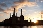 The iconic Art Deco Batersea Power Station at the edge of the River Thames at sunset. The four towers silhouetted against the sun and clouds.