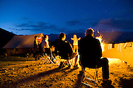 Trekkers bathed in the warm glow of a roaring campfire near the bottom of the Matho Valley, after a successful attempt to summit Stok Kangri, Ladakh