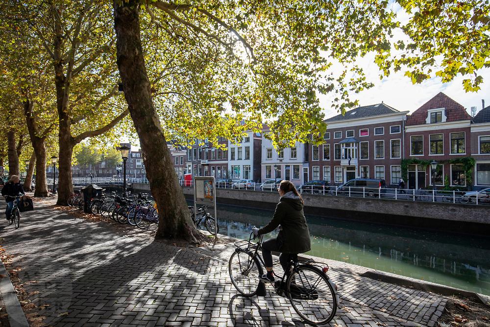 Fietsers rijden op een zonnige herfstdag langs de Oudegracht in Utrecht.<br /> <br /> On a sunny autumn day cyclist ride along the Oudegracht in Utrecht.