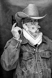 The Covid-19 Cowboy - model dressed in American Old West attire with bandana across the face in outlaw fashion in hopes of addressing mask wearing concerns associated with the Novel Coronoavirus pandemic that spans the earth in the spring of 2020.