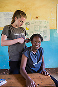 Cathryn Tomnay cutting the hair of Frida Francis during their lunch break in Mbulu. ICS Raleigh SWASH (school water, sanitation and hygiene plan) project. Mbulu, Manyara district, Tanzania. Working in partnership with the Diocese of Mbulu Development Department (DMDD); part of Caritas Tanzania.