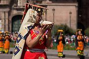 "A Virgin of the Sun holding an offering of maize to the sun. Inti Raymi ""Festival of the Sun"", Plaza de Armas, Cusco, Peru."