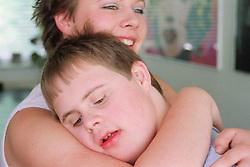 Teenage girl hugging brother with Downs Syndrome smiling,