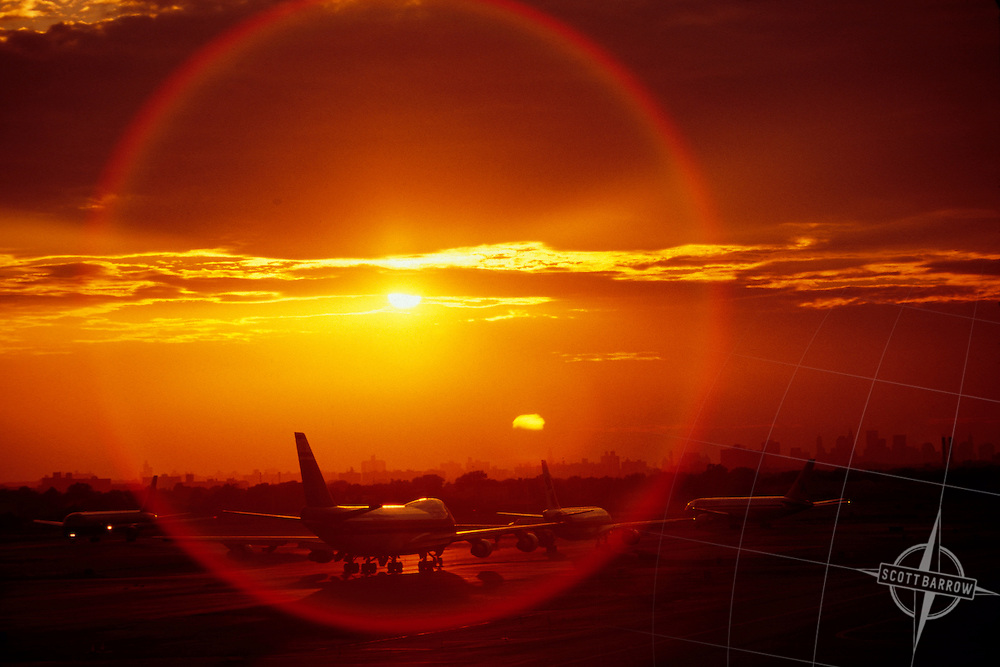 Planes lining up for takeoff at JFK Airport in New York City.  Sunset.