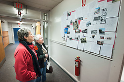 """Ora's daughters, Claudette Saunders and Lorraine Benoit look at students writings about the book """"Ora's Boy"""" outside a classroom at Laconia High School on Thursday, December 20, 2012.  (Alan MacRae/for the Laconia Daily Sun)"""