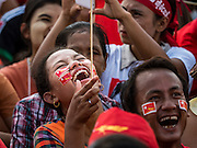 01 NOVEMBER 2015 - YANGON, MYANMAR:  A woman laughs at a joke made from the stage while crowd waits for Aung San Suu Kyi at the NLD's last election rally of the 2015  election in the Yangon suburbs Sunday. Political parties are wrapping up their campaigns in Myanmar (Burma). National elections are scheduled for Sunday Nov. 8. The two principal parties are the National League for Democracy (NLD), the party of democracy icon and Nobel Peace Prize winner Aung San Suu Kyi, and the ruling Union Solidarity and Development Party (USDP), led by incumbent President Thein Sein. There are more than 30 parties campaigning for national and local offices.   PHOTO BY JACK KURTZ