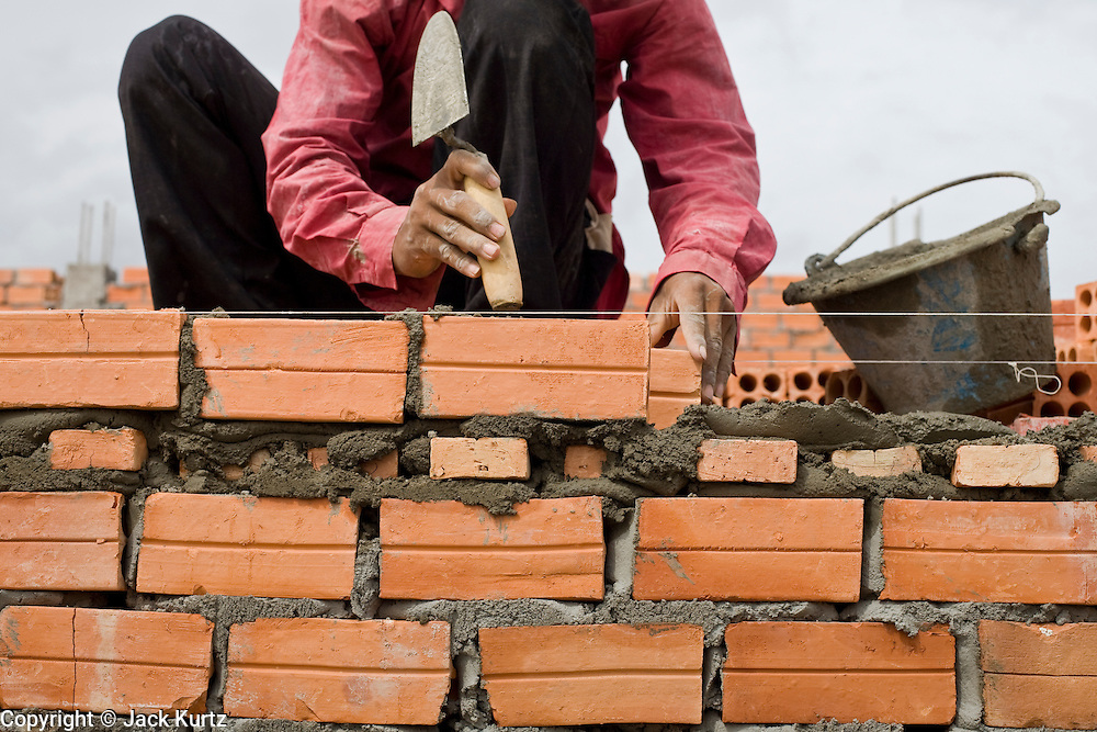 30 JUNE 2006 - PHNOM PENH, CAMBODIA: A construction worker in Phnom Penh uses locally made bricks on a high end construction project building homes for expatriots and wealthy Cambodians. According the United Nations Food and Agricultural Organization, there are more than 70 brick factories in Phnom Penh and its environs. Environmentalists are concerned that the factories, most of which burn wood in their kilns, contribute to deforestation in Cambodia. They are encouraging factory owners to switch to burning rice husks, as brick kilns in neighboring Vietnam do. The brick factories are kept busy feeding Phnom Penh's nearly insatiable appetite for building materials as the city is in the midst of a building boom brought by on economic development and the need for new office complexes and tourist hotels.  PHOTO BY JACK KURTZ
