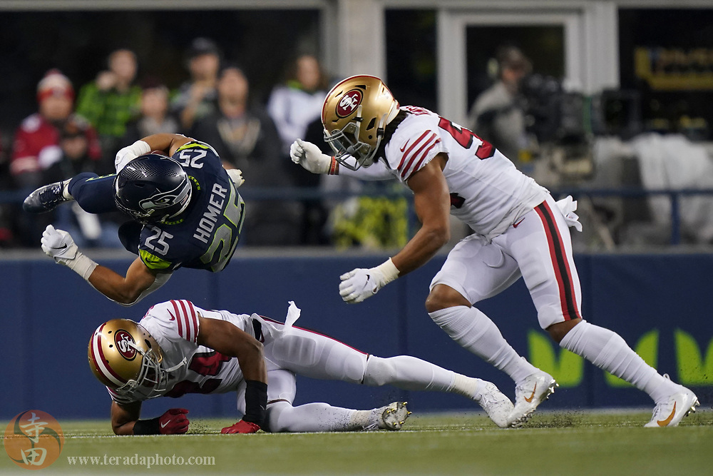 December 29, 2019; Seattle, Washington, USA; Seattle Seahawks running back Travis Homer (25) is tackled by San Francisco 49ers defensive back K'Waun Williams (24) and middle linebacker Fred Warner (54) during the second quarter at CenturyLink Field.