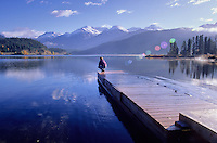 Woman crouches on dock, autumn morning, at Green Lake, in Whistler, BC Canada.