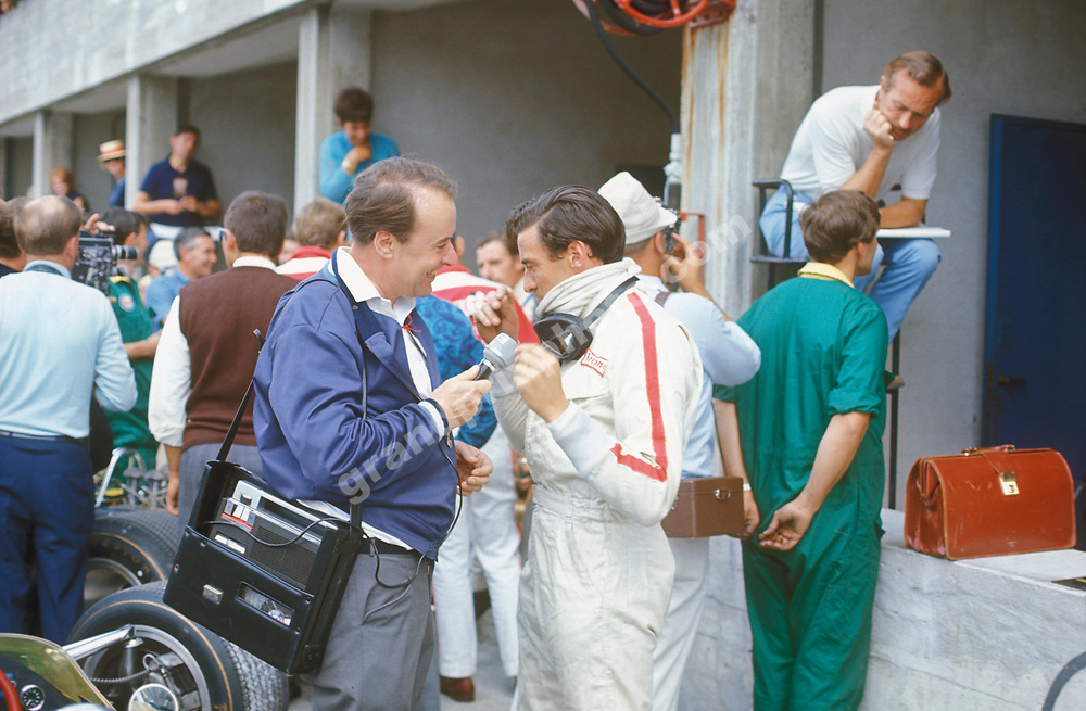 Lotus driver jim Clark during a radio interview in the pits at Monza before the 1967 Italian Grand Prix. In the background is Lotus team principal Colin Chapman. Photo: Grand Prix Photo