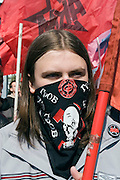 Moscow, Russia, 09/05/2006..Masked members of Red Youth Vanguard march flanked by OMON riot police, as Russians celebrated the 61st anniversary of the end of the Second World War, generally referred to in Russia as the Great Patriotic War.