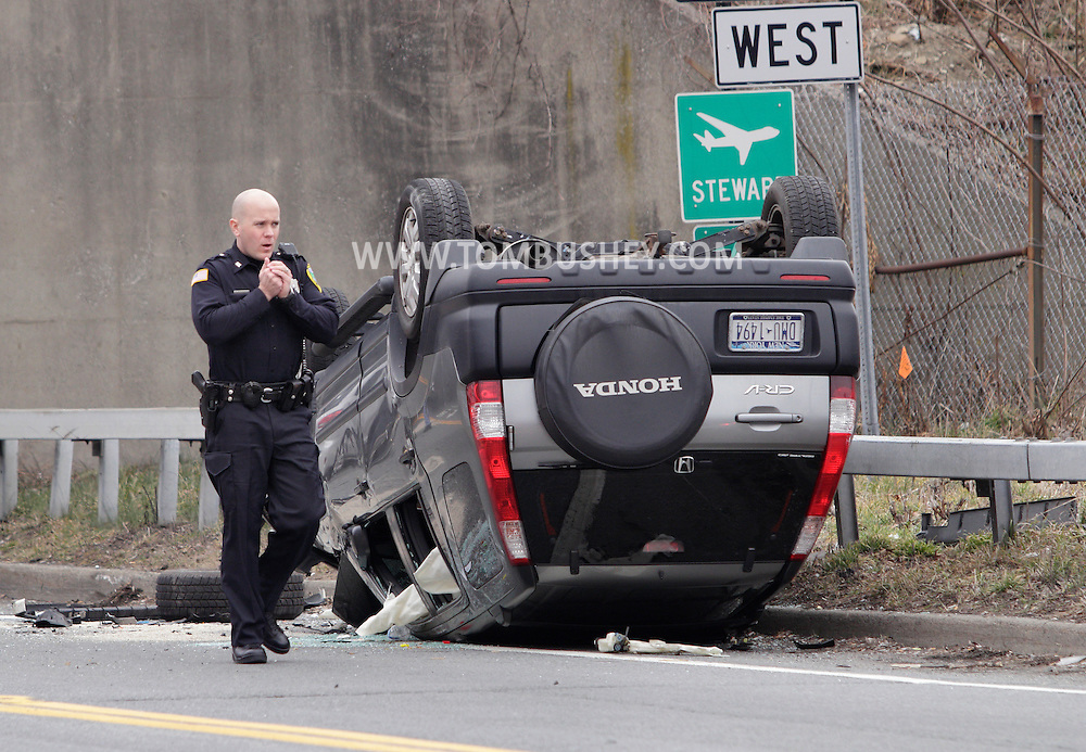 New Windsor, New York - A police officer walks past the scene of a rollover motor vehicle accident on Route 207 on Feb. 18, 2012.