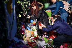 © Licensed to London News Pictures. 28/12/2016. London, UK. Member of the public take pictures of tributes, left outside the London home of singer and musician George Michael, in Highgate, North London. Pop superstar George Michael died on Christmas day at his Oxfordshire home on the River Thames aged 53. Photo credit: Ben Cawthra/LNP