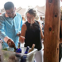Mauricio Mota and Katy Good choosing a wine at the wine tasting event at Red Rock Park, Wednesday Aug. 8, 2018.