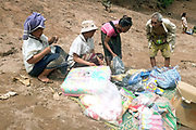 The small monthly market at the remote and roadless Khmu village of Ban Seua-Thiek, Phongsaly province, Lao PDR. The market traders travel along the Nam Ou visiting different villages selling every kind of Chinese and Vietnamese product that one might need - like biscuits and flip flops, washing powder and salt. Ban Seua-Thiek will soon be temporarily relocating away from the Nam Ou river due to the construction of the Nam Ou Cascade Hydropower Project Dam 5.