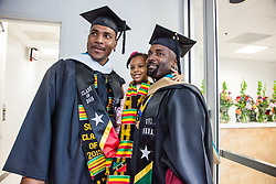 Lyle Q. Gumbs, right, poses with his god-daughter Dorothy Ann Hutchins-Joseph with friend Shawn G. Seabrookes.  Fifty-first annual University of the Virgin Islands  Commencement Exercises.  UVI Sports & Fitness Center.  St. Thomas, VI.  14 May 2015.  © Aisha-Zakiya Boyd