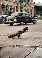 Damaged fire hydrant and American car, Havana, Cuba