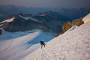 Jim Prager stands contemplating the mountain scenery as he descends steep snow at the foot of Mount Challenger, Picket Range, North Cascades National Park, Washington.