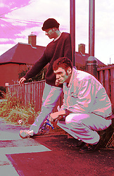 Two unemployed youths loitering around housing estate looking bored,