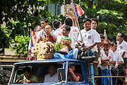 13 JUNE 2013 - YANGON, MYANMAR: People in a truck go to a Buddhist temple for a festival in Yangon. Yangon, formerly Rangoon, is Myanmar's commercial capital and used to be the national capital. The city is on the Irrawaddy River and has a vibrant riverfront.    PHOTO BY JACK KURTZ