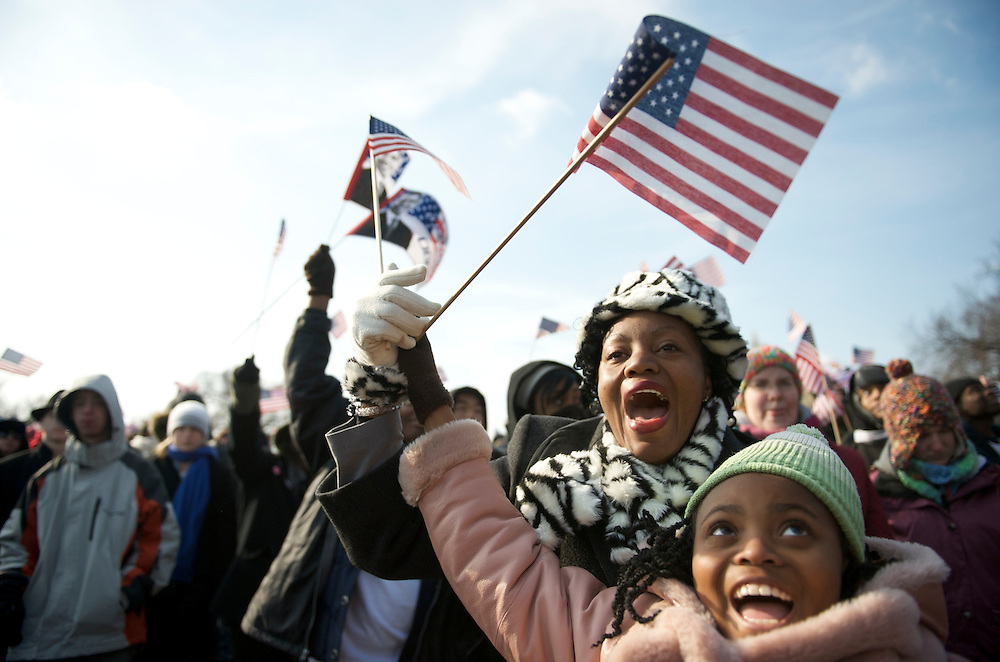 Waving flags wildly, mother and daughter, 10, Jackie and Kitty Hickmen, who had traveled from South Carolina, take in Barack Obama's Presidential Inauguration ceremony.  An estimated two million people flocked to Washington D.C. for the ceremony, enduring freezing temperatures to witness Obama take the oath of office becoming the first African-American to become President, the 44th in the history of the United States of America.
