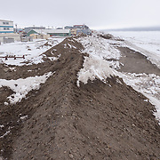 A sand barrier piled along the shores of Barrow, Alaska, to reduce seawater from entering the streets of the city.