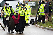 Hertfordshire Police officers arrest an anti-HS2 activist who blocked one of several entrances to the Chiltern Tunnel South Portal site for the HS2 high-speed rail link for the entire day on 9 October 2020 in West Hyde, United Kingdom. The protest action, at the site from which HS2 Ltd intends to drill a 10-mile tunnel through the Chilterns, was intended to remind Prime Minister Boris Johnson that he committed to remove deforestation from supply chains and to provide legal protection for 30% of UK land for biodiversity by 2030 at the first UN Summit on Biodiversity on 30th September.