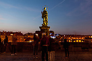 """Crowds are passing and photographing the statue of  """"John of Nepomuk"""" which is an outdoor sculpture, installed in 1683 on the north side of the Charles Bridge in Prague, Czech Republic."""