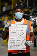 Takunda Mupudzi is pictured inside Amazon Fulfillment Center Man 3 Near Bolton.  He has worked at Amazon for 11 weeks, he is from Saddleworth. He was asked to write two ways he felt the COVID 19 Lockdown had impacted himself.