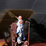 Two workers spray painting the side of a ship in a ship yard