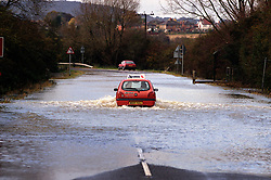 Learner driver attempts to negotiate a road flooded by the River Soar, Leicestershire, England, UK.