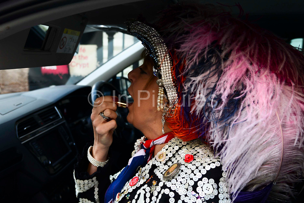 A pearly Queen applies her lipstick ahead of a churcg service at St Martin-in-the-Fields church for their annual Harvest Festival on 6th October 2019 in London, United Kingdom. The tradition of the Pearly Kings and Queens originated in the 19th century when London street sweeper Henry Croft decorated his uniform and began collecting money for charity. The annual harvest festival sees Pearly Kings and Queens gather to celebrate the autumn harvest with a church service.
