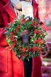 Carol holding holly wreath. Ilex