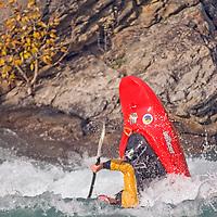 Play boat kayaker Mikkel St. Jean-Duncan (MR) wave surfing on Kananaskis River, Kananskis Provincial Park, near Banff and Calgary, Alberta, Canada