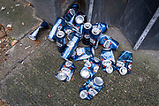 A collection of discarded Kronenbourg 1664 extra-strength lager beer cans remain on the ground in a side street off New Oxford Street in Londons West End, on 10th September 2021, in London, England.