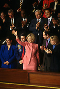 Hillary Clinton waves after being acknowledged by President Bill Clinton prior to delivering  the State of the Union address to Congress January 27, 1998 in Washington, D.C. Standing with the first lady from left to right are: Elaine Kinslow, Space Shuttle Commander Col. Robert Cabana, Dr. Harold Varmus, director of the National Institutes of Health, and Tipper Gore.