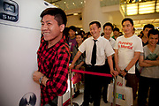 Man squeezes himself through a gap in an oversized cell phone in order to win a prize. Shoppers watch a massive PR promotional push by cell phone company Mororola. Following a stage presentation with models and large screens, the mobile phone giant has staff selling phones to customers as well as fun and giving away gifts by way of mass marketing. Crowds gathered to watch and buy. Xidan is one of the main commercial shopping area in the Xicheng district of Beijing, China. With Joy City as it's centerpiece, a 13-story coplex of western and Chinese shops. This is a shoppers haven as modern consumerism and commerce have a strong grip on Beijing's shop hungry crowds.