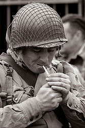 Reneactors portraying members of the US 82nd 'All American' Airborne Division lights a cigarette while taking part in living history displays and Battle re-enactments at Fort Paull Near Hull in May 2019